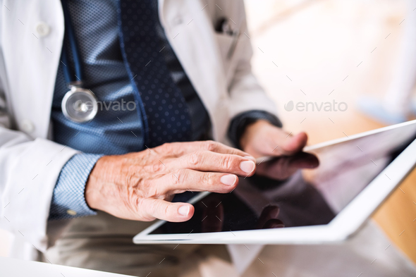 Senior doctor with tablet working at the office. - Stock Photo - Images