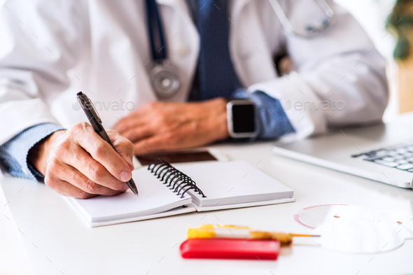 Senior doctor working at the office desk. - Stock Photo - Images