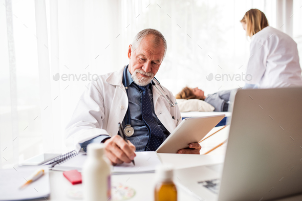 Senior doctor with tablet in his office. - Stock Photo - Images
