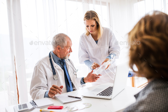 Senior doctor examining a senior woman in office. - Stock Photo - Images