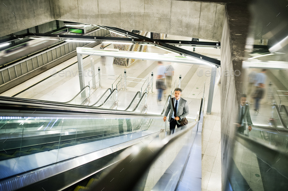 Businessman on an escalator on a metro station. - Stock Photo - Images