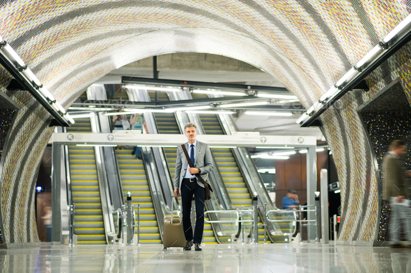 Businessman in front of escalators on a metro station. - Stock Photo - Images