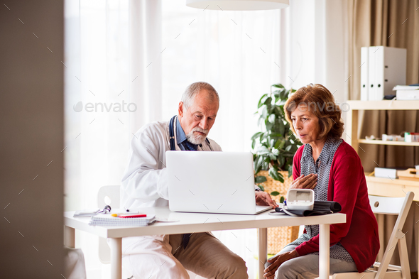 Doctor with laptop talking to a senior woman in office. - Stock Photo - Images