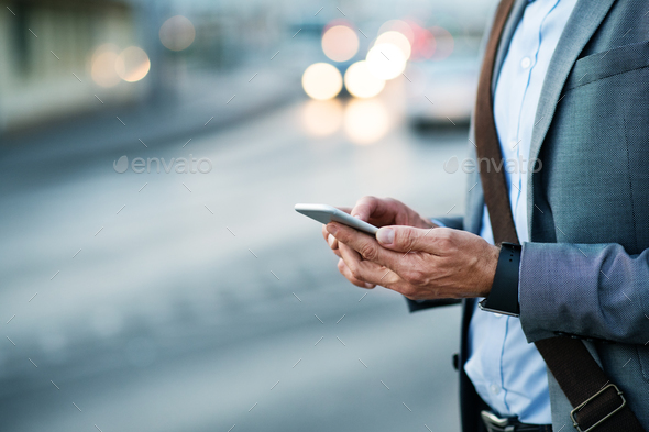 Businessman with smartphone in a city. - Stock Photo - Images