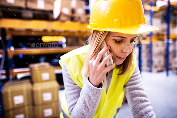 Female warehouse worker with smartphone. - Stock Photo - Images