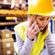 Female warehouse worker with smartphone. - PhotoDune Item for Sale