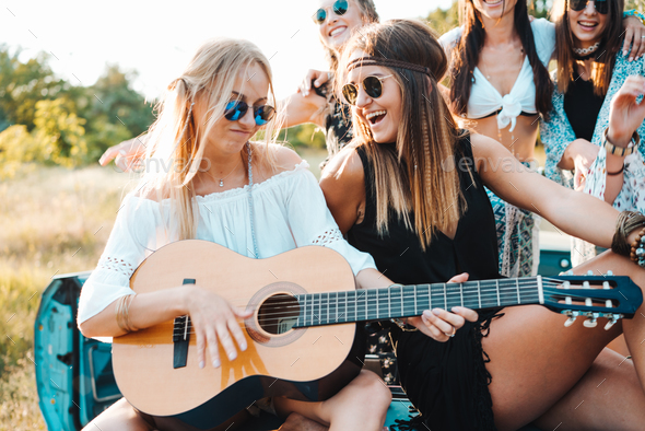 Girls are sitting on the trunk with a guitar - Stock Photo - Images