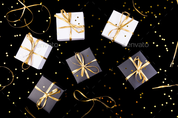 Black and white gift boxes with gold ribbon on shine background. Flat lay. - Stock Photo - Images
