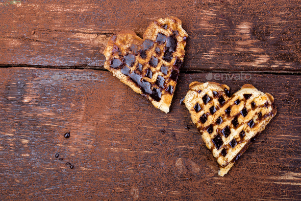 Two belgian heart shaped waffle with chocolate on wooden background. Flat lay. Copy space - Stock Photo - Images