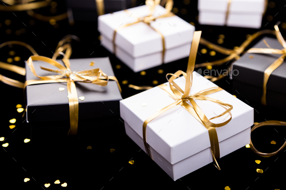 Black and white gift boxes with gold ribbon on shine background. Close up. - Stock Photo - Images