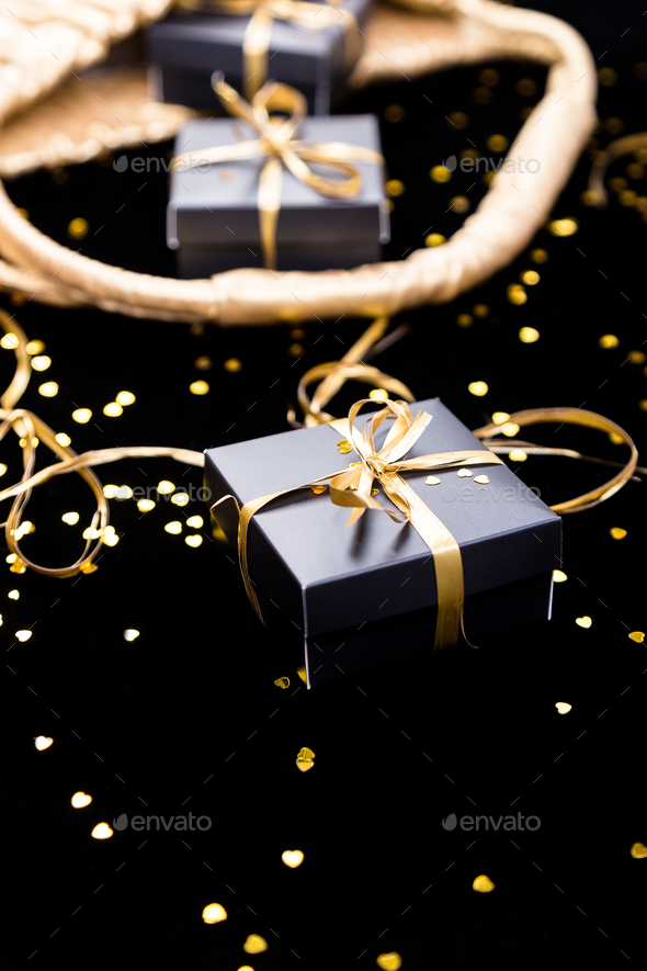 Black gift boxes with gold ribbon pop out from golden bag on shine background. Close up. - Stock Photo - Images
