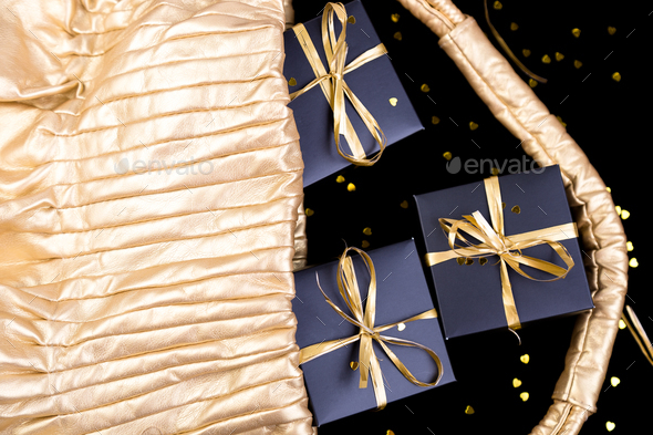 Black gift boxes with gold ribbon pop out from golden bag on shine background. Flat lay. - Stock Photo - Images