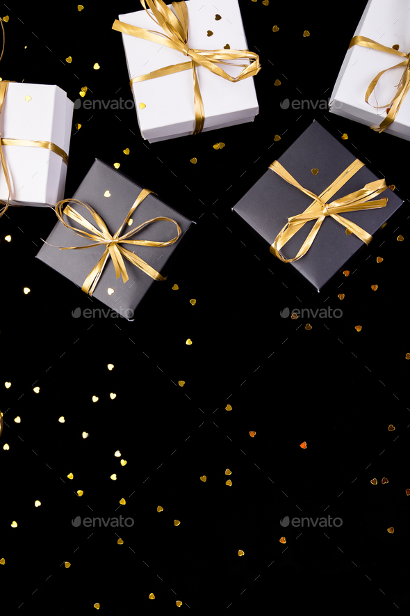 Black and white gift boxes with gold ribbon on shine background. Flat lay. Copy space. - Stock Photo - Images