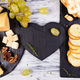 Cheese plate. Assortment of cheese with walnuts, bread an honey on stone slate plate. - PhotoDune Item for Sale