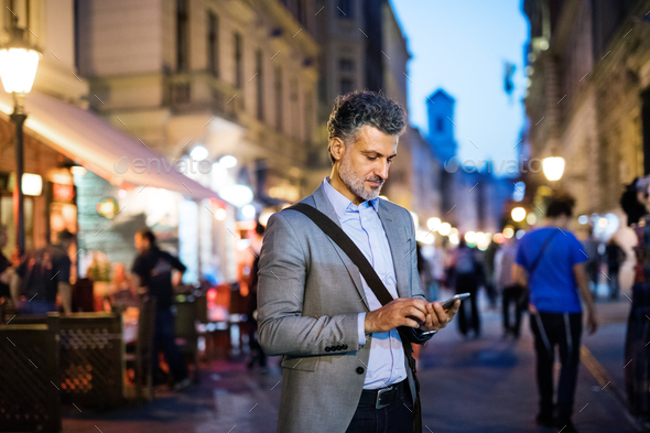 Mature businessman with a smartphone in a city. - Stock Photo - Images