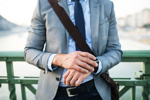 Businessman with smartwatch in a city. - Stock Photo - Images