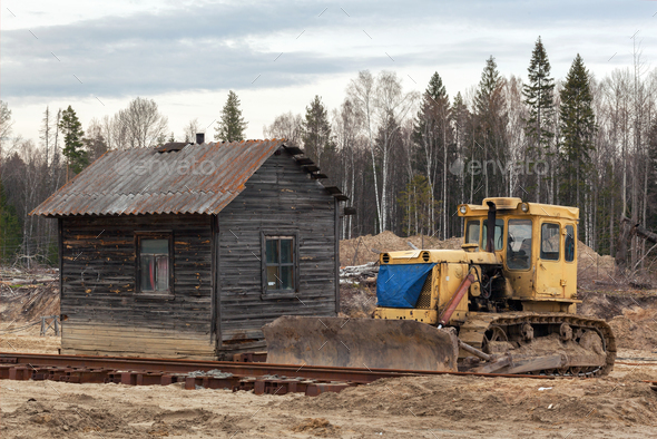 Yellow bulldozer in the sand near the  wooden house - Stock Photo - Images