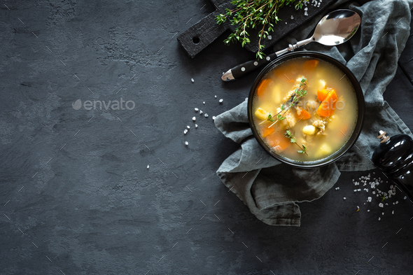 Fresh fish soup in bowl on dark background, top view - Stock Photo - Images