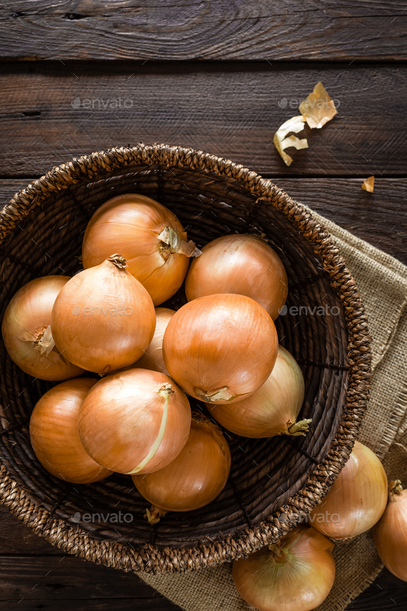 Fresh onion in basket on wooden table, top view - Stock Photo - Images