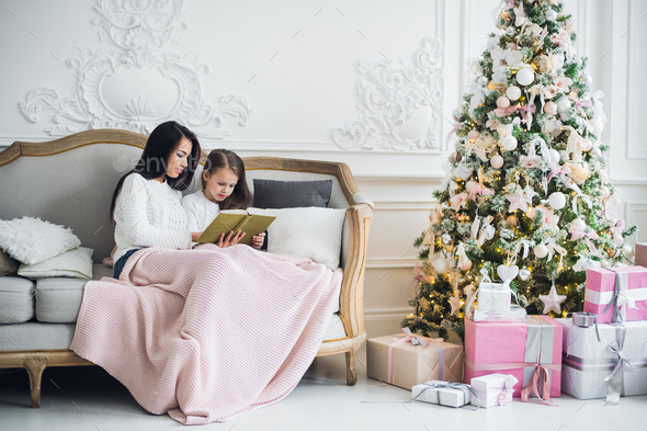 Two happy girls, mother and daughter siting on a sofa in Christmas decorated room. - Stock Photo - Images