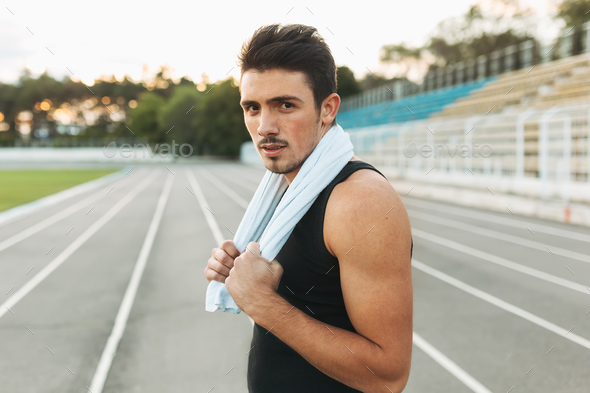 Portrait of a fitness man with towel on shoulders resting after - Stock Photo - Images