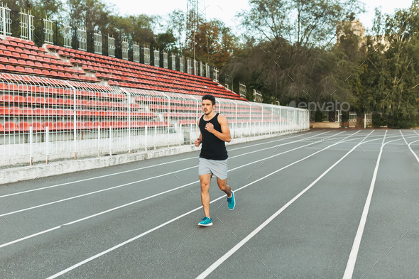 Young athletic man running on the stadium in the morning - Stock Photo - Images