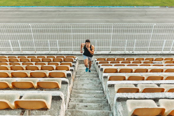 Image of young athletic man running by ladder at the stadium out - Stock Photo - Images