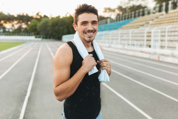 Portrait of a smiling fitness man with towel on shoulders - Stock Photo - Images