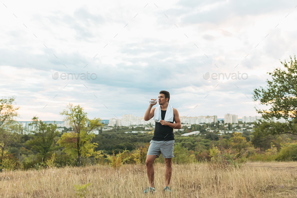 Healthy man drinking water on nature while resting - Stock Photo - Images