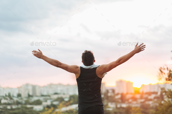 Young man raising hands over sunset sky after training - Stock Photo - Images