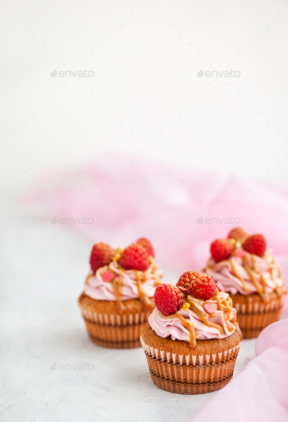 Raspberry and caramel cupcakes on white background - Stock Photo - Images