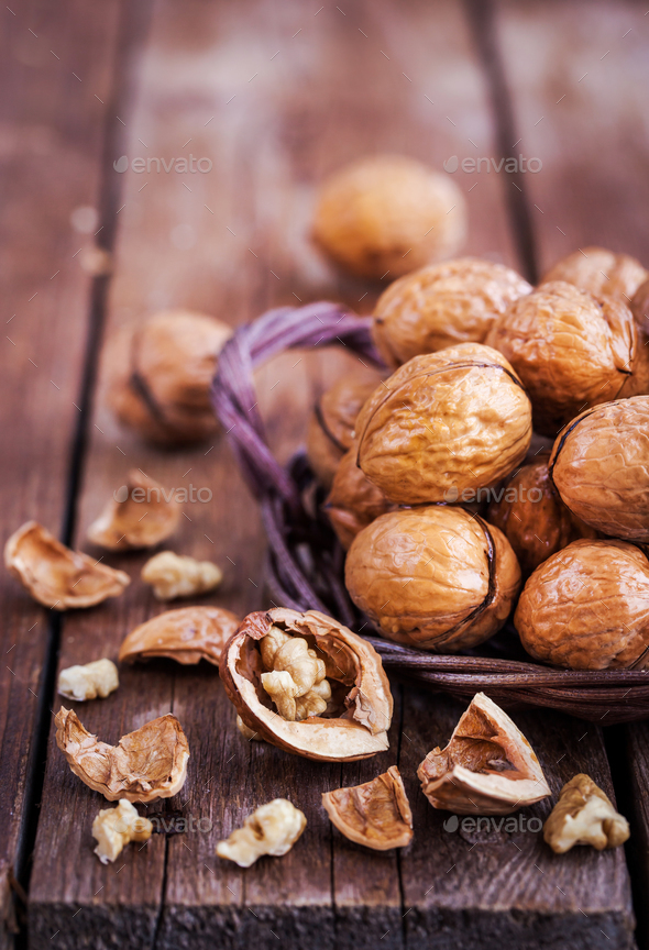 Whole walnuts in basket on rustic old wooden table - Stock Photo - Images