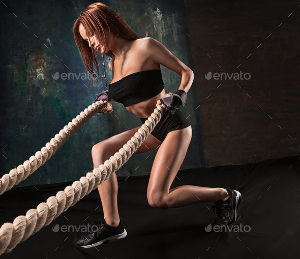 The strong young woman pulling rope at a gym - Stock Photo - Images
