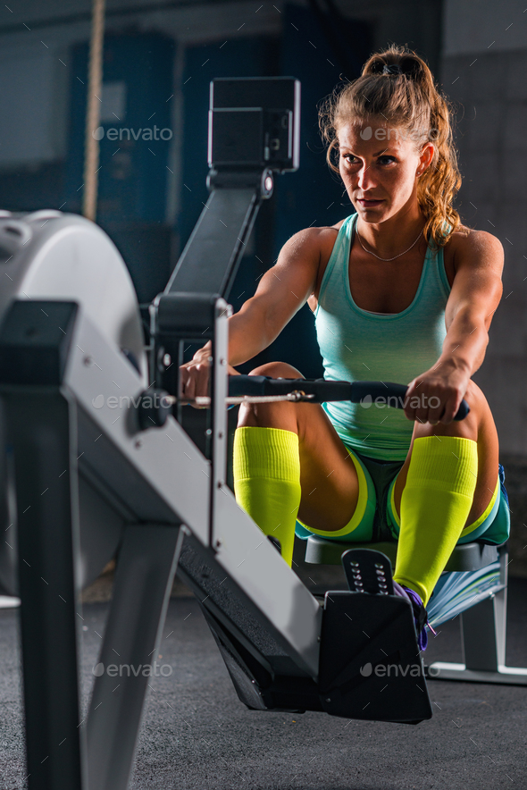Woman athlete exercising on rowing machine - Stock Photo - Images
