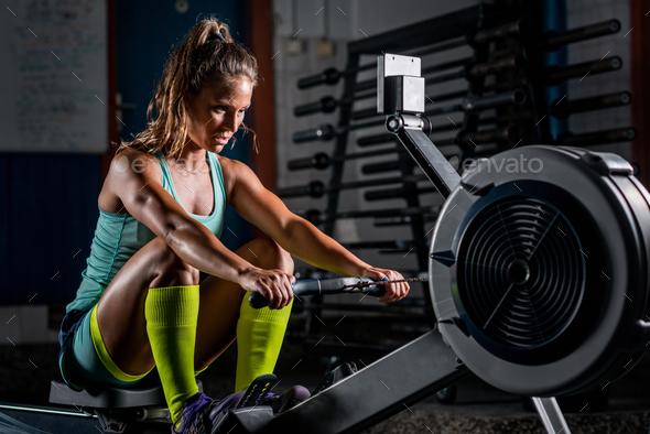 Woman athlete exercising on rowing machine - Stock Photo - Images