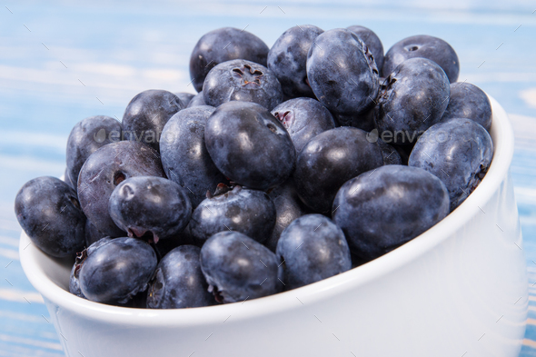 Fresh blueberries in glass bowl on blue boards, natural source of minerals, healthy dessert concept - Stock Photo - Images