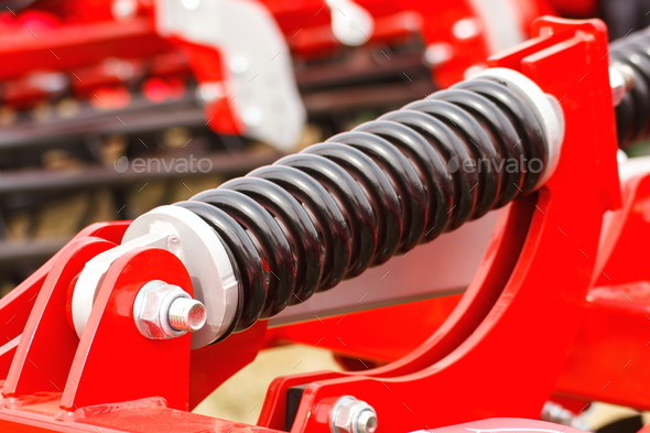 Steel spring on industrial or agricultural machinery, technology and engineering - Stock Photo - Images