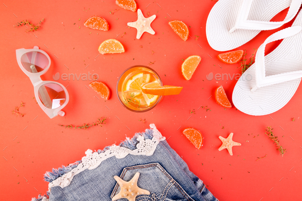 Summer vacation. Orange fruit cocktail, detox water near white flip flops, shorts and sunglases. - Stock Photo - Images