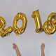 Hands holding golden 2018 balloons, new year concept - PhotoDune Item for Sale