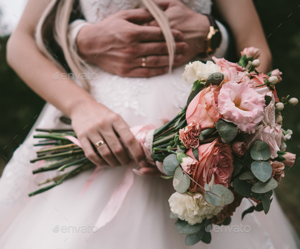 The bridegroom embraces the bride's waist, - Stock Photo - Images