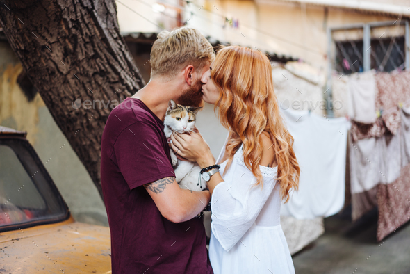 beautiful couple and cat posing outdoors - Stock Photo - Images