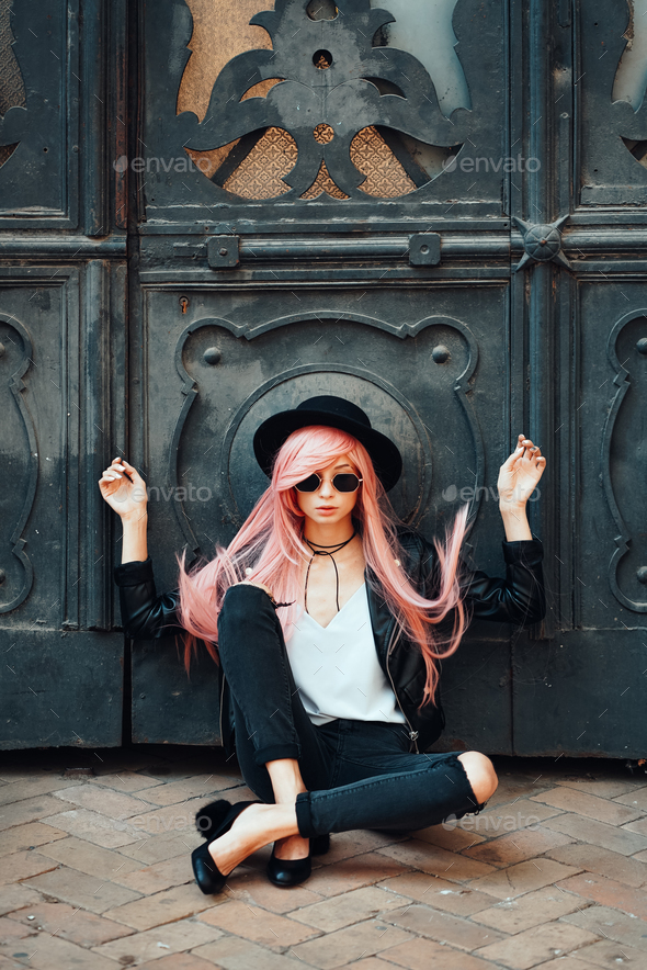 girl with pink hair posing on city street - Stock Photo - Images