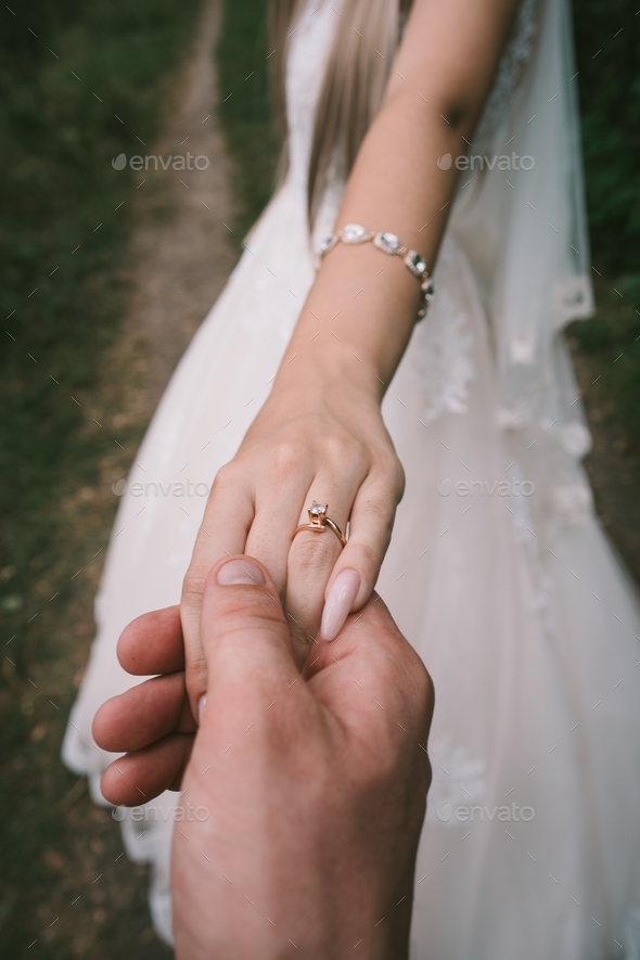 Groom's hand holding bride's hand. - Stock Photo - Images