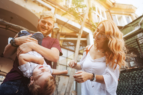 Happy parents playing with little son outdoor - Stock Photo - Images
