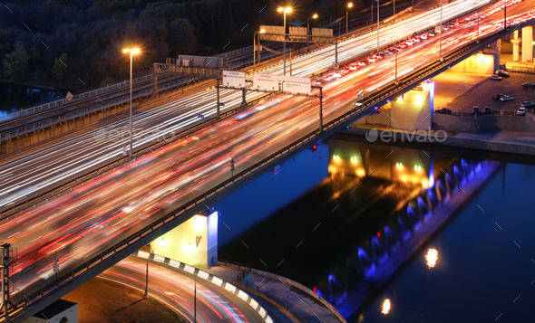 Road bridge across the river at night, view from above. light trails of cars on a highway. - Stock Photo - Images