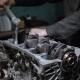 Mechanic Repairs Engine Block in a Garage.