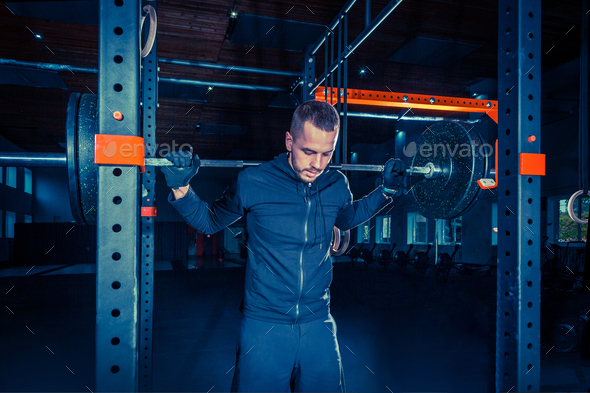 Portrait of super fit muscular young man working out in gym with barbell - Stock Photo - Images