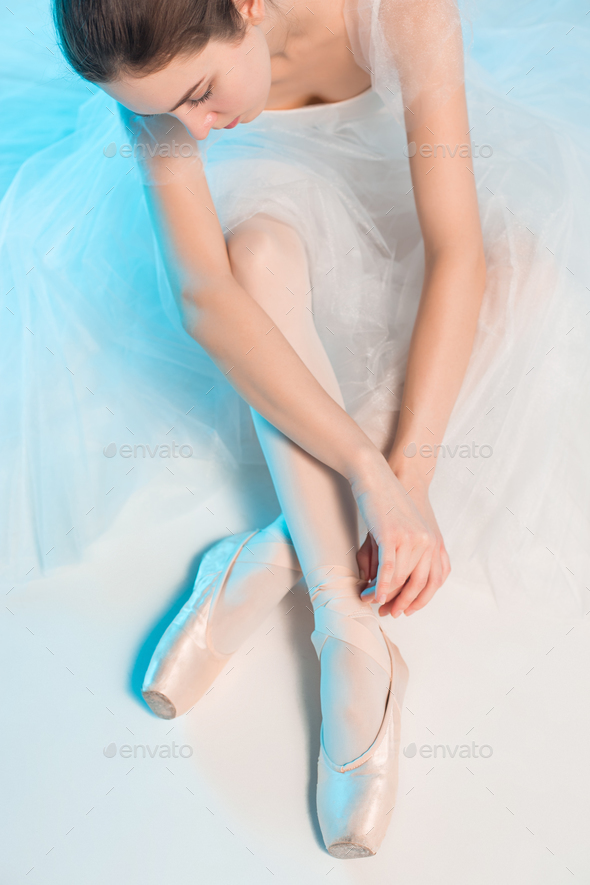 Young and incredibly beautiful ballerina is sitting in a blue studio - Stock Photo - Images