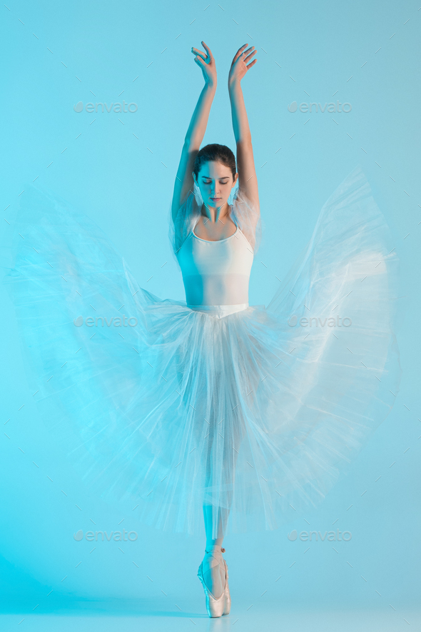 Young and incredibly beautiful ballerina is dancing in a blue studio - Stock Photo - Images