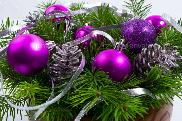 Christmas arrangement with purple balls in the wooden bowl - Stock Photo - Images